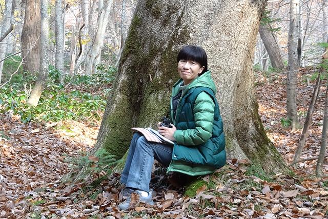 筆者近影。落ち葉の降り積もる知床の森の中で。